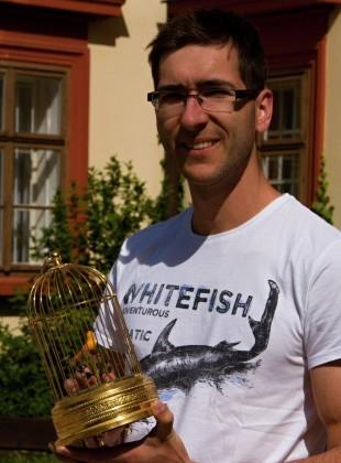 Autor výstavy Patrik Pařízek s klíckou s mechanickým ptáčkem